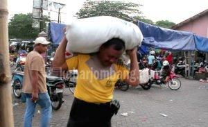 Aiptu Khamim memanggul sendiri bumbu dagangannya ke pasar. (FOTO: AAN)