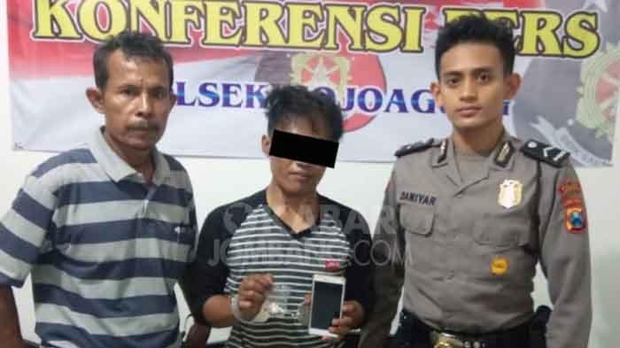Tersangka Kris bersama barang buktinya, saat dirilis petugas di Polsek Mojoagung, Jombang.