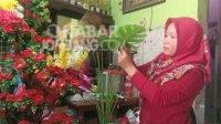 Hajar, warga Tunggorono, Jombang sedang merangkai bunga.
