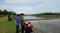 Warga menyaksikan proses evakuasi mayat tanpa identitas di Dam Klaci Desa Brodot Kecamatan Bandarkedungmulyo Kabupaten Jombang, Selasa (23/3/2021). Kabarjombang.com/Diana Kusuma Negara/