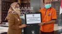 Bupati Jombang Mundjidah Wahab (kiri) menyerahkan bantuan secara simbolis kepada pelaku usaha kecil. KabarJombang.com/Anggraini Dwi/