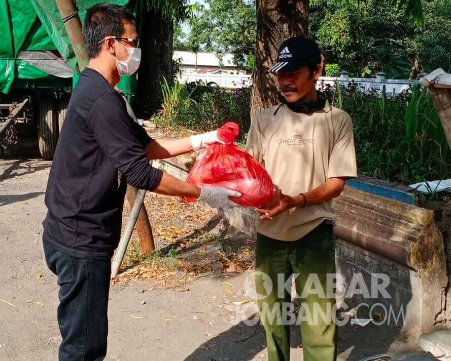 CEO Kelompok Faktual Media (KFM), Adi Susanto (kiri) menyerahkan bantuan paket sembako ke tukang becak di Jombang, Jumat (16/7/2021). KabarJombang.com/Diana Kusuma/