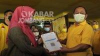 Ketua DPD Golkar Provinsi Jawa Timur, Sarmuji (kanan) menyerahkan secara simbolis kartu vaksin covid-19 kepada peserta di DPD Partai Golkar Jombang, Sabtu (25/9/2021). KabarJombang.com/Daniel Eko/