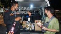 Kasat Sabhara Polres Jombang, Iptu Mulyani (kiri) mengamankan puluhan botol miras saat patroli Prokes.