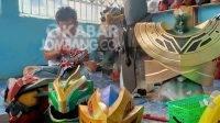Tampak Rezza Andi Faizal (28), salah satu pengrajin Cosplay asal Desa Sambungdukuh, Kabupaten Jombang saat melukis helm Cosplay milik pelanggan, Minggu (24/10/2021).